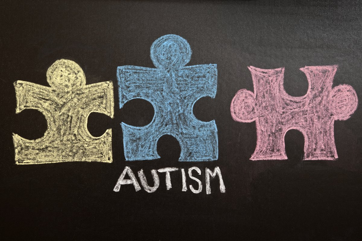 A yellow, blue and red puzzle pieces and the word Autism drawn on a chalkboard.