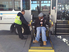 man getting off a bus using a lift